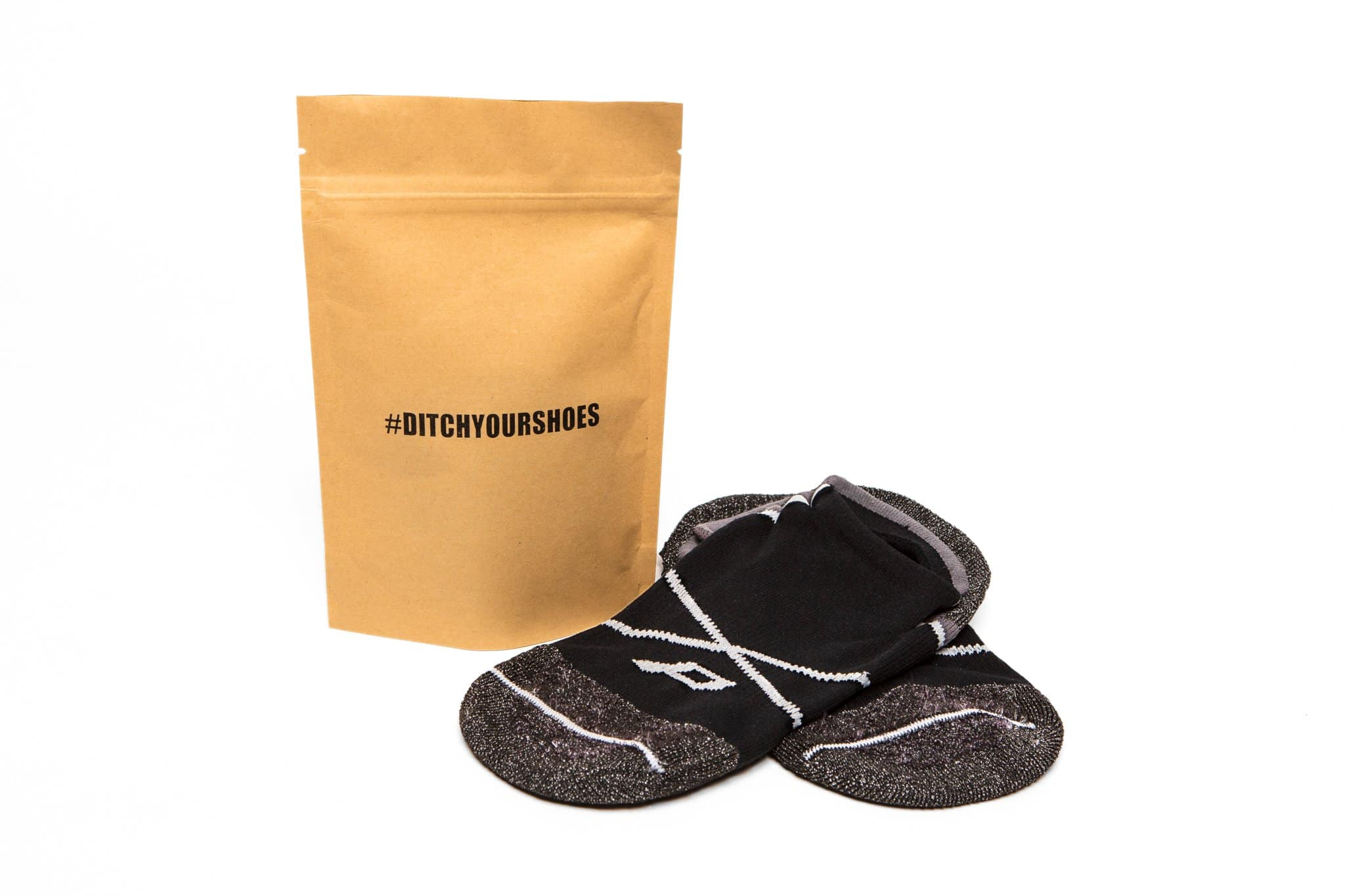 Pedestal Footwear socks sitting next to a manilla bag that says #DITCHYOURSHOES