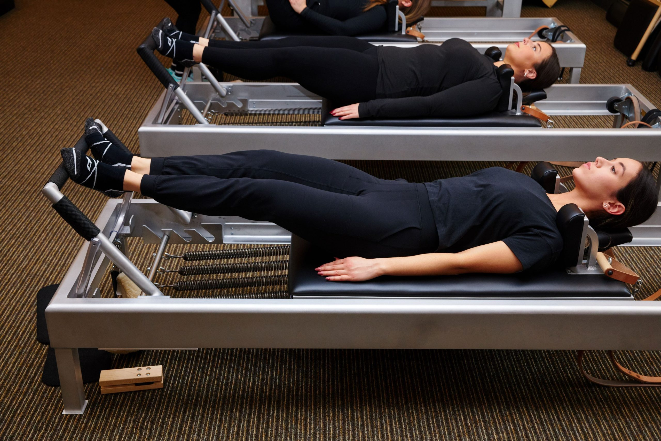 3 women on benches working out with pedestal socks on