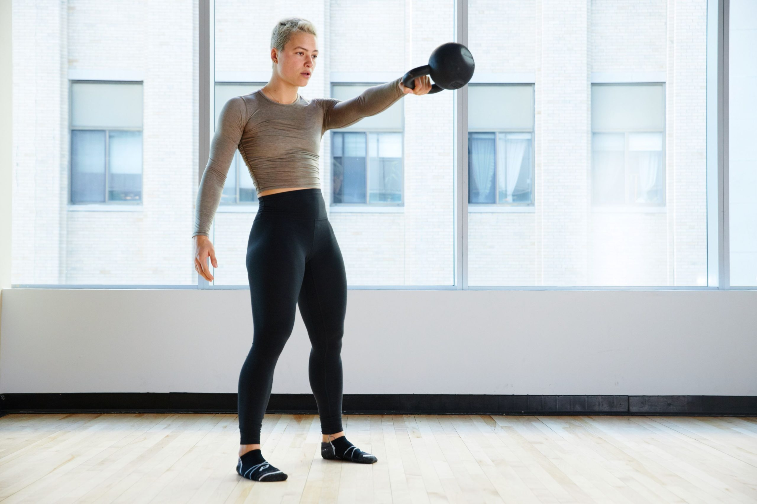 Kelley Matthews working out with a kettlebell and pedestal socks on