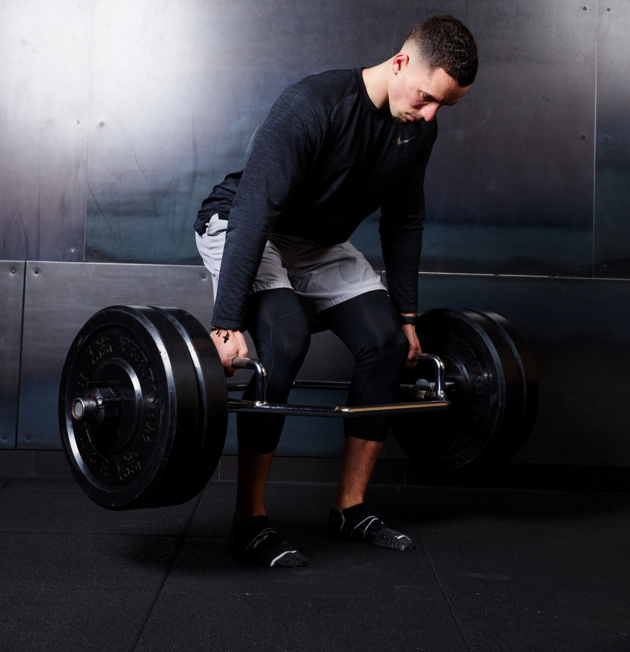Man in the gym mid-deadlift with pedestal socks on